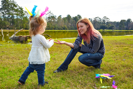 boroughs: Mother and daughter playing with color feathers in a park lake