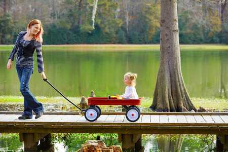 lagoon: Kid girl and mother walking in the park lake with pull cart