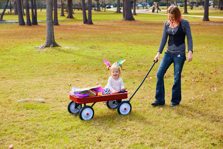 boroughs: Kid girl and mother walking in the park with pull cart Stock Photo