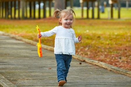 boroughs: Kid baby girl with toy guitar walking fun in the autumn park