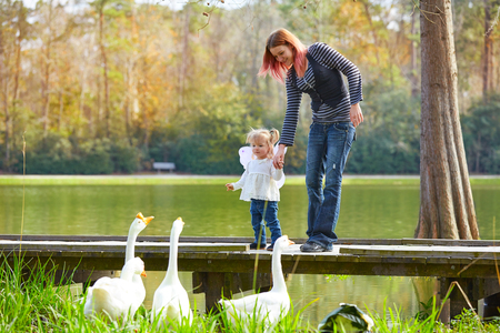 boroughs: Kid girl and mother playing with ducks in the park lake