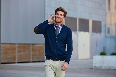 casual office: Young businessman talking smartphone phone walking on the street
