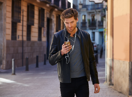 hombre escribiendo: Young man listening music with smartphone earphones walking in the street
