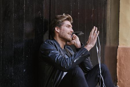Giovane con auricolari smartphone seduti in porta nera strada