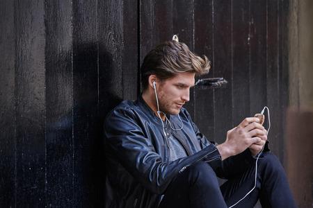 escuchando musica: joven de la música que escucha del hombre con los auriculares de teléfonos inteligentes que se sientan en la puerta de calle negro