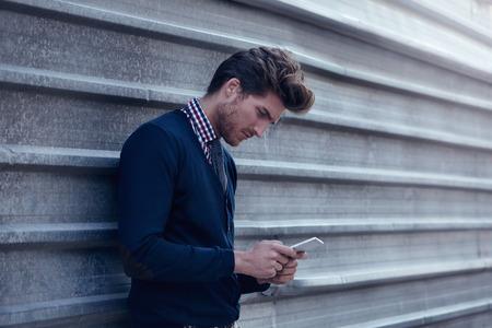 personen: Jonge zakenman texting smartphone telefoon op de straat metalen hek