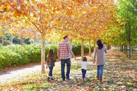 family walking in an autumn park with fallen fall leaves Foto de archivo