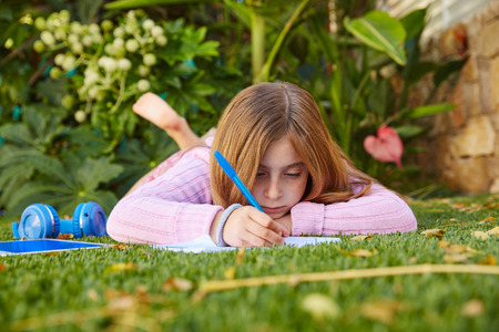 girl lying: Blond kid girl homework lying on grass turf writting notebook