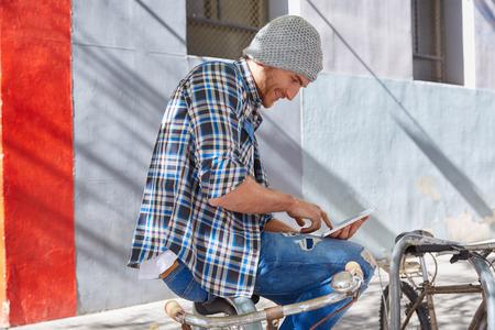 hombres guapos: Young man using tablet pc touch in a bicycle casual clothing outdoor Foto de archivo