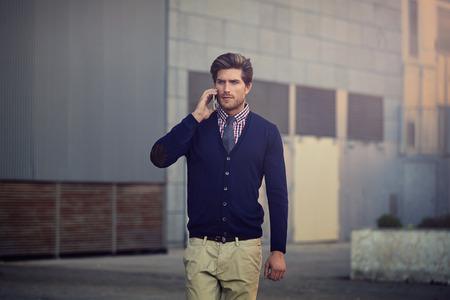 elegant business man: Young businessman talking smartphone phone walking on the street