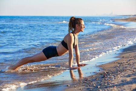 Pilates yoga workout exercise outdoor on the beach sand photo