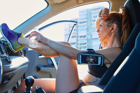 Runner woman relaxing after workout sitting inside a car photo