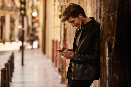 escuchando musica: joven de la música que escucha del hombre con los auriculares de teléfonos inteligentes en la calle