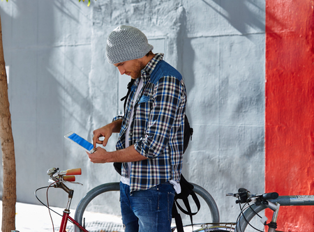 young male: Young man using tablet pc touch in a bicycle casual clothing outdoor Stock Photo