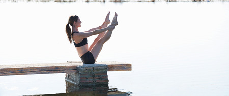 Pilates yoga workout exercise outdoor in the lake pier photo