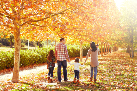 walking baby: family walking in an autumn park with fallen fall leaves Stock Photo