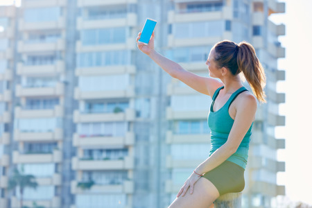 Runner girl having a rest shooting selfie with smartphone outdoor building park photo