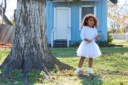 yard stick: Kid toddler girl with branch stick playing outdoor park latin ethnicity