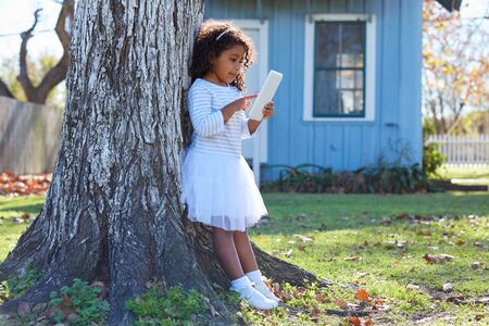latin ethnicity: Kid toddler girl with tablet pc playing outdoor park latin ethnicity Stock Photo