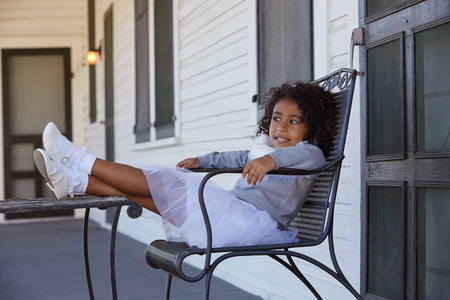 latin ethnicity: Kid toddler girl sitting in the park house porch legs on table latin ethnicity Stock Photo