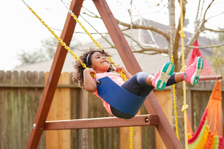 latin ethnicity: Kid toddler girl swinging on a playground swing in the backyard latin ethnicity Stock Photo