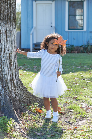 latin ethnicity: Kid toddler girl with autumn leaf magic wand playing outdoor park latin ethnicity Stock Photo