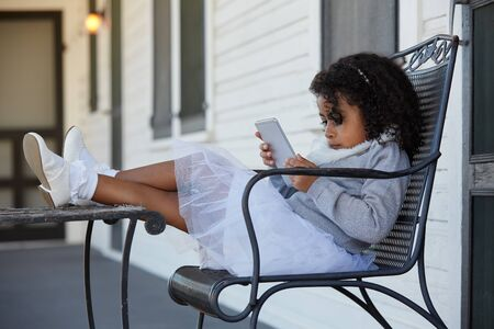 latin ethnicity: Kid toddler girl sitting in the park house porch playing with smartphone latin ethnicity Stock Photo