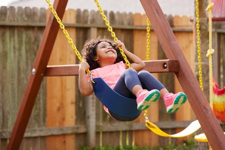 Kid toddler girl swinging on a playground swing in the backyard latin ethnicity Standard-Bild