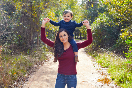 hombros: kid boy sitting on mother shoulders walking in the park trail Foto de archivo