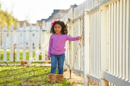 latin ethnicity: Toddler kid girl portrait in a park fence latin ethnicity