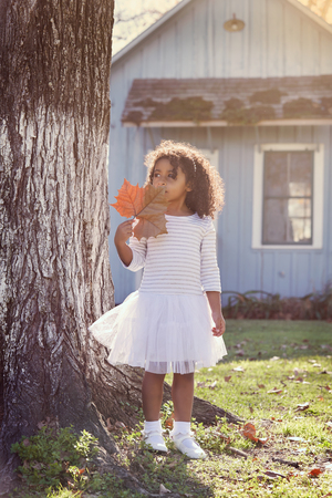 latin ethnicity: Kid toddler girl with autumn leaf playing outdoor park latin ethnicity
