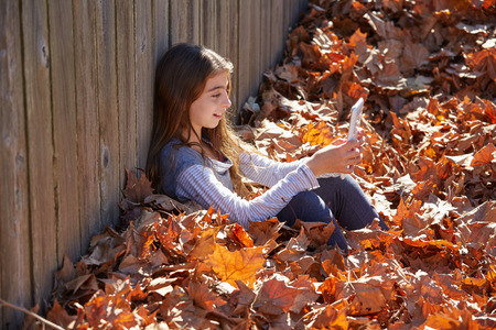 tween: Tween kid girl playing tablet pc in autumn leaves Stock Photo