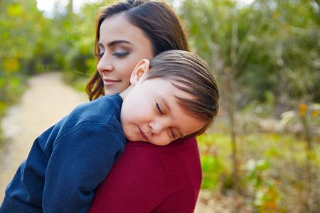 mama e hijo: Madre sosteniendo a dormir niño de niño en el hombro en el parque Foto de archivo