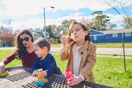 family in park: Mother daughter and son family in the park blowing soap bubbles Stock Photo