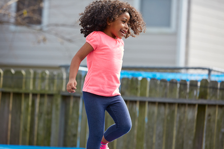 latin ethnicity: Kid toddler girl jumping on a playground in the backyard latin ethnicity Stock Photo