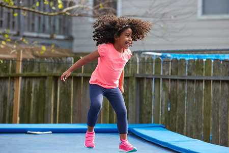 latin ethnicity: Kid toddler girl jumping on a trampoline playground in the backyard latin ethnicity
