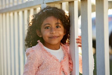 latin ethnicity: Happy toddler kid girl portrait in a park fence latin ethnicity