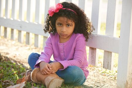 latin ethnicity: Sad toddler kid girl portrait in a park fence latin ethnicity