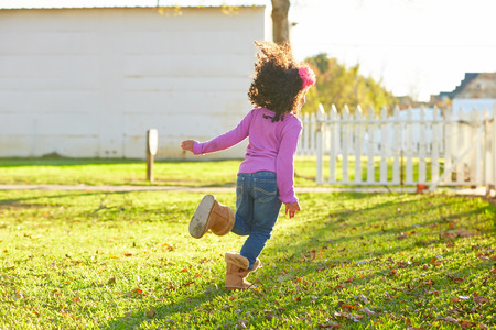 latin ethnicity: kid girl toddler playing running in park rear view latin ethnicity Stock Photo