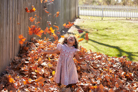latin ethnicity: Toddler kid girl playing with autumn leaves latin ethnicity
