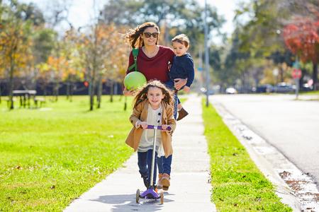 mama e hijo: hija de la madre y la familia hijo en el parque caminando con la bola y la vespa del patín