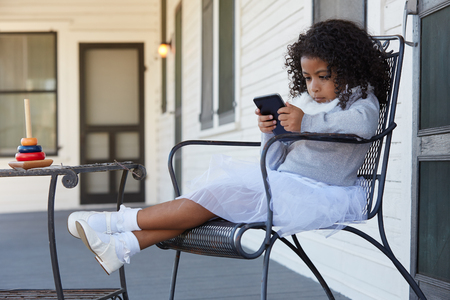 niñas jugando: Kid toddler girl sitting in the park house porch playing with smartphone latin ethnicity Foto de archivo