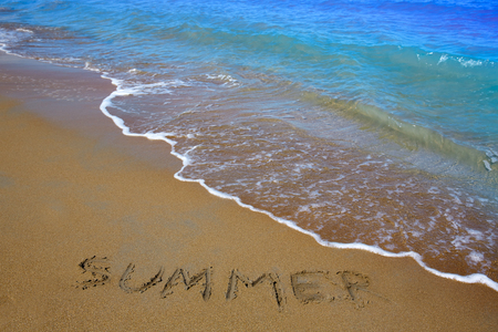 Summer spell written word in sand of a beach in vacation Banco de Imagens