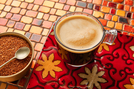 Coffee glass cup with cream on tiles red brown golden table