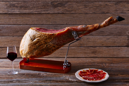 Iberian ham pata negra from Spain with red wine on wood background