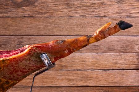 Iberian ham pata negra from Spain on wood background Stock Photo