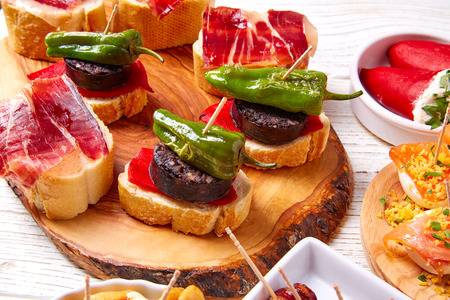 Tapas mix and pinchos food from Spain recipes also pintxos on a white wood board Stock Photo