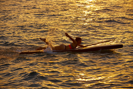SUP Stand up Surf girl swimming lying on board at sunset Stock Photo