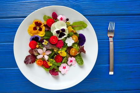 Ensalada de flores comestibles en un plato en la mesa de madera azul con un tenedor Foto de archivo - 74821975