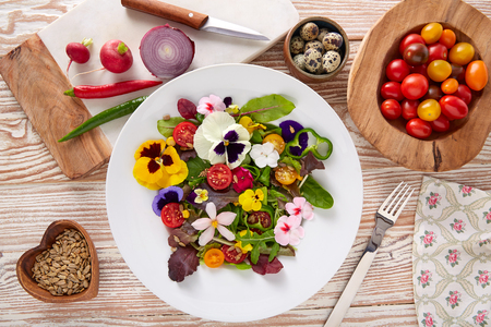 Eetbare bloemensalade in een bord met ingrediënten